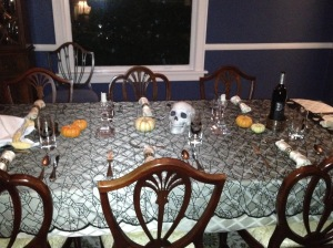 Low-lighting, candles, a spiderweb table dressing & skull from Target plus mini-pumpkins from Trader Joe's give a Halloween air to the table